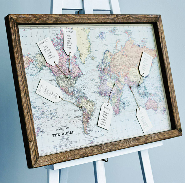 World map table plan with guest names on luggage labels.